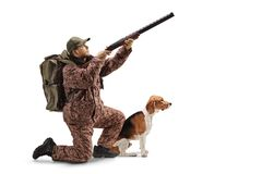 Hunter kneeling with a shotgun, aiming upwards and a beagle dog next to him. Full length shot of a hunter kneeling with a shotgun, aiming upwards and a beagle royalty free stock images
