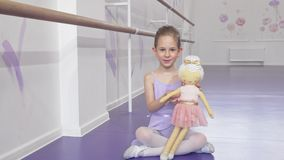 Full length shot of a lovely little ballerina waving to the camera playing with a doll. Adorable little ballerina girl in leotard playing with her doll stock video footage