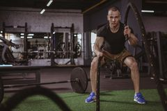 Male crossfit athlete working out with battle ropes at gym stock image