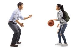 Man and a female student playing basketball stock photography