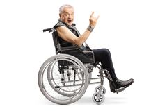 Mature man in a wheelchair making a rock and roll hand sign and looking at the camera stock images