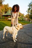 Full-length shot of pretty healthy young lady walking in the morning in park with dog Royalty Free Stock Photos