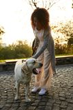 Full-length shot of pretty healthy young lady walking in the morning in park with dog Stock Images