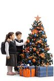 Full length shot of a schoolgirl and schoolboy decorating a Christmas tree stock image