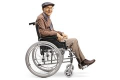 Senior man in a wheelchair smiling at the camera royalty free stock image