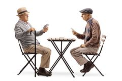 Two senior men playing cards at a table. Full length shot of two senior men playing cards at a table isolated on white background royalty free stock photography