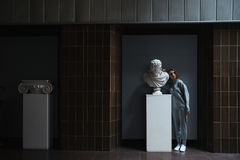 Full-length shot of woman standing near bust. Full-length shot of woman wearing casual standing near bust in museum Royalty Free Stock Images