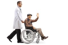 Young male doctor pushing a senior man sitting in a wheelchair and waving stock images
