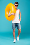 Full-length shot of young man with swimming circle posing at camera. Full-length shot of young brunette man with swimming circle posing at camera isolated over stock photography