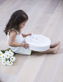 Full length side of little girl opening gift box on floor at home Royalty Free Stock Photography