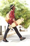 Side portrait of cool young african guy in hat walking outdoors with skateboard and bag. Full length side portrait of cool young african guy in hat walking Royalty Free Stock Photography