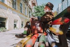 Stylish elderly man sitting on a bench royalty free stock photography