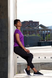 Full length side of young african woman leaning to wall outdoors after workout Stock Photo