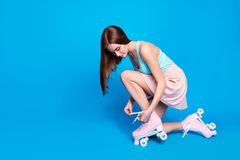 Full length side profile body size photo beautiful floor she her lady hands tied fixing retro rollers laces together fit. Ideal body wear casual street summer royalty free stock image