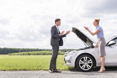Full length side view of business couple arguing over broken car at countryside Stock Photos