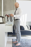 Full length side view of businessman selecting socks at home Stock Photos