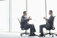 Full-length side view of businessmen discussing while sitting on office chairs by window Royalty Free Stock Photo