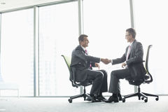Full-length side view of businessmen shaking hands while sitting on office chairs by window Royalty Free Stock Image