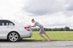 Full length side view of businesswoman pushing broken down car at countryside Royalty Free Stock Image