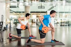 Determined young man exercising Russian twist. Full length side view of a determined young men holding a weight plate, while exercising Russian twist for core royalty free stock photo
