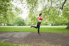 Full length side view of fit woman jogging in park Stock Photo