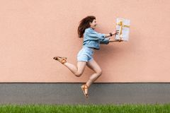 Full length side view of happy excited beautiful woman in casual jeans denim style in summertime standing near sandybrown wall,. Holding gift box and jumping royalty free stock photo
