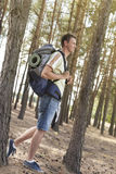 Full length side view of male hiker with backpack walking in forest Stock Images