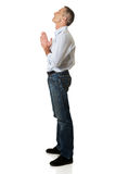 Full length side view of a man praying to God Stock Photography