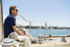 Full-length side view of man sitting on yacht Stock Image