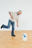 Full length side view of a mature man mopping the floor. In a room Stock Photography