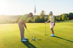 Man ready to hit the golf ball while exercising with his game pa. Full length side view of a men ready to hit the golf ball into the hole while exercising the Stock Photos