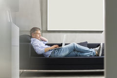 Full-length side view of Middle-aged man using laptop while lying on sofa Stock Images
