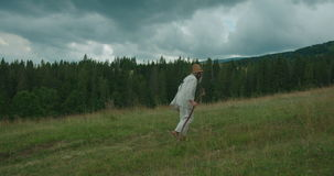 The full-length side view of the old man in old clothes, with long beard walking along the green mountains with the help. Of the cane stock video footage