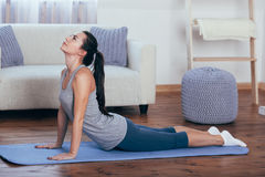 Full length side view portrait of beautiful young woman working out at home, doing yoga or pilates exercise on wooden Stock Image