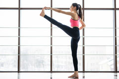 Full length side view portrait of beautiful young woman working out in luxury fitness center, doing yoga hasta padangusthasana Stock Photos