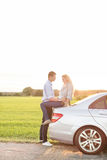 Full length side view of romantic young couple by car at countryside Royalty Free Stock Photos