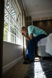 Full length side view of serious senior man sitting on bed by window. At home Royalty Free Stock Photo