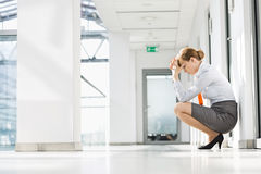 Full-length side view of stressed businesswoman crouching at office hallway Royalty Free Stock Image
