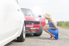 Full-length side view of tensed woman looking at damaged cars on road Royalty Free Stock Photos