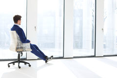 Full length side view of thoughtful young businessman sitting on chair by windows in new office Royalty Free Stock Photo