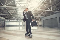 Demure businessman talking by mobile. Full length side view unshaven earnest male worker speaking by phone while going on hoverboard indoor. Orderly employer Royalty Free Stock Photos