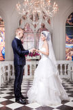 Full length side view of wedding couple exchanging rings in church Royalty Free Stock Photo
