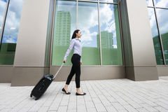 Full length side view of young asian businesswoman walking with luggage on sidewalk against building Royalty Free Stock Photo