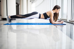 Full-length side view of young beautiful woman in sportswear doing plank while standing in front of window at gym Royalty Free Stock Photo