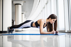 Full-length side view of young beautiful woman in sportswear doing plank while standing in front of window at gym Stock Images