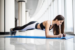 Full-length side view of young beautiful woman in sportswear doing plank while standing in front of window at gym Royalty Free Stock Photos