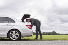 Full length side view of young businessman looking in car trunk at countryside Royalty Free Stock Image