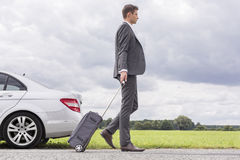 Full length side view of young businessman with luggage leaving broken down car at countryside Royalty Free Stock Photography