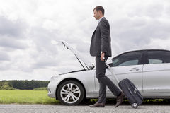 Full length side view of young businessman with luggage walking by broken down car at countryside Stock Images