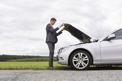 Full length side view of young businessman opening broken down car hood at countryside Royalty Free Stock Photos